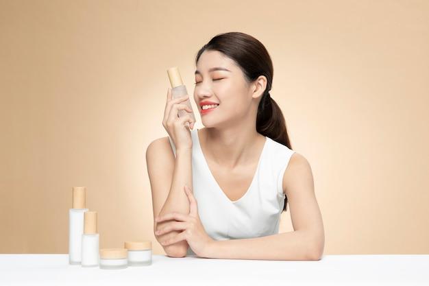 Linda mulher asiática segurando uma garrafa de produto em um fundo laranja