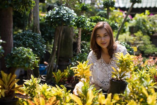 Linda mulher asiática, selecionando flores na loja de flores, estilo de vida da dona de casa moderna.