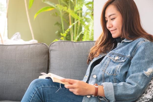 Linda mulher asiática sentado e lendo um livro de romance vintage no sofá