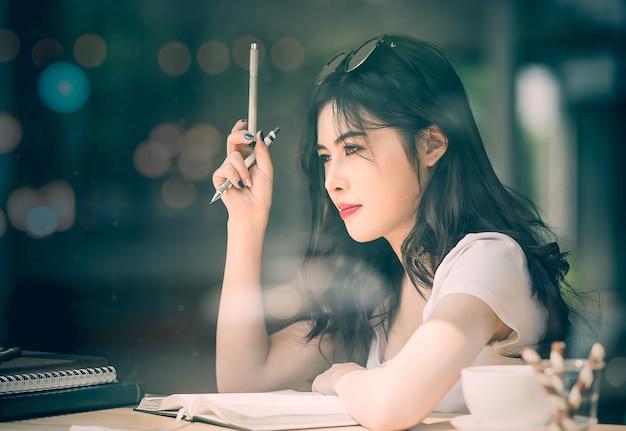 Linda mulher asiática sentado e olhando do lado de fora