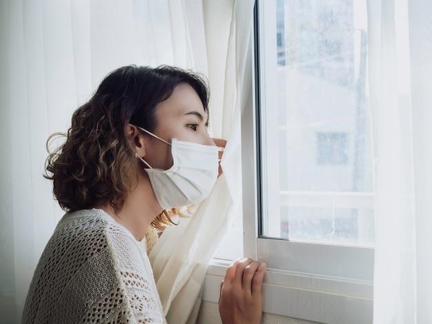Linda mulher asiática solitária usando máscara médica, olhando pela janela