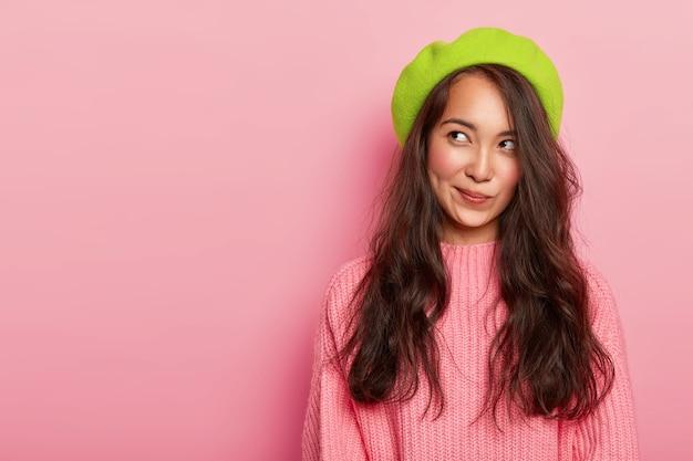 Linda mulher asiática sonhadora perdida em pensamentos, olha para o lado e franze os lábios, usa boina verde e suéter de tricô