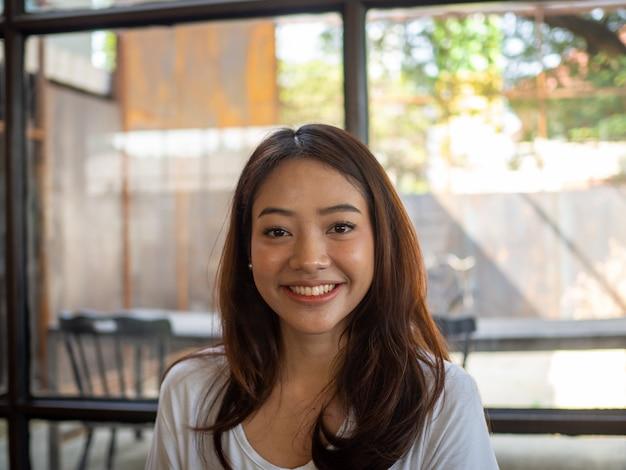 Linda mulher asiática sorri em uma cafeteria