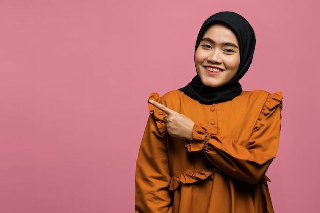 Linda mulher asiática sorridente apontando para o espaço vazio