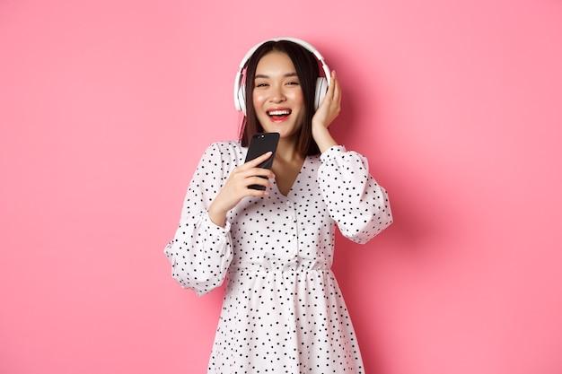 Linda mulher asiática sorridente cantando uma música no microfone do smartphone, jogando karaokê e usando fones de ouvido, em pé sobre um fundo rosa