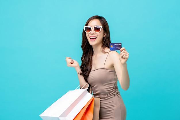 Linda mulher asiática sorridente com as compras
