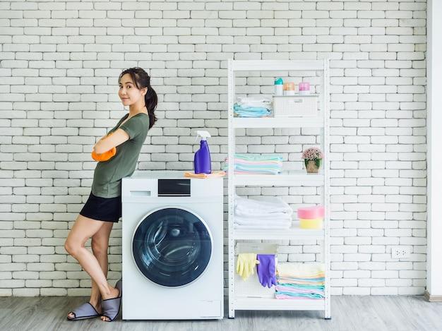 Linda mulher asiática sorridente, dona de casa feliz usando luvas protetoras de borracha laranja em pé com os braços cruzados ao lado da máquina de lavar na parede de tijolos brancos