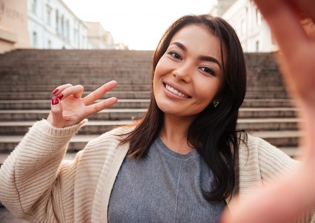 Linda mulher asiática sorridente, mostrando o gesto de paz enquanto estiver a tomar selfie no telemóvel nas escadas da cidade