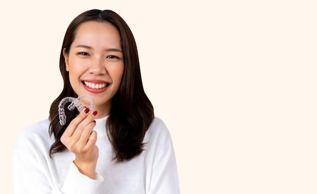 Linda mulher asiática sorrindo com a mão segurando o retentor do alinhador dental (invisível)