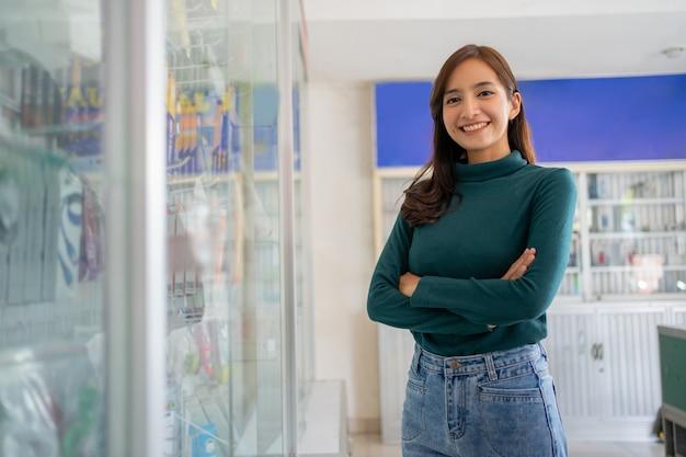 Linda mulher asiática sorrindo com as mãos cruzadas perto da vitrine de acessórios para celular