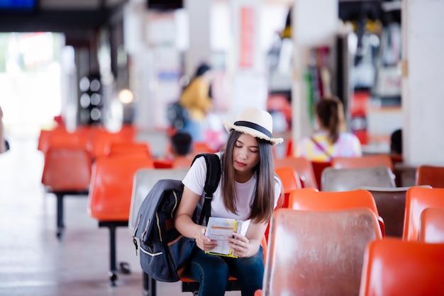 Linda mulher asiática sorrindo com mapa e bolsa na estação de ônibus