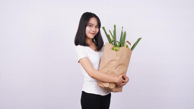 Linda mulher asiática sorrindo com um saco de papel de legumes frescos com uma superfície branca isolada
