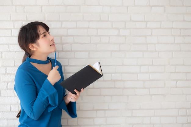 Linda mulher asiática sorrindo em pé pensando e escrevendo o caderno sobre cimento branco fundo de concreto