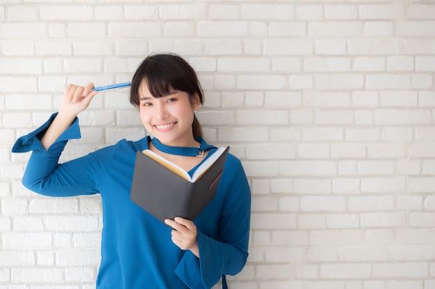 Linda mulher asiática sorrindo em pé pensando e escrevendo o caderno