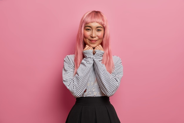 Linda mulher asiática tem longos cabelos rosa, pele saudável, beleza natural, mantém as mãos sob o queixo, sorri suavemente