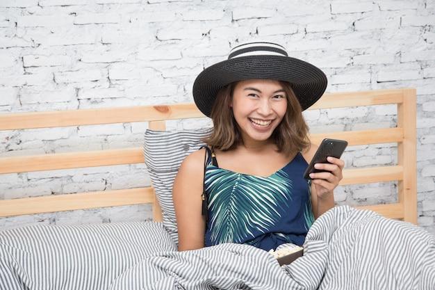 Linda mulher asiática tocando tablet telefone inteligente e comendo pipoca na cama