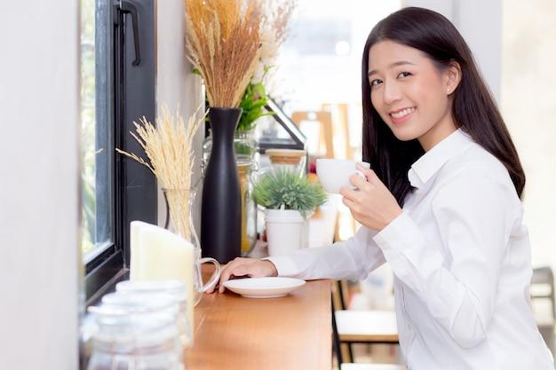 Linda mulher asiática tomando café e sorrir de manhã.