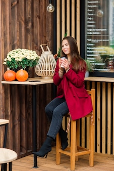 Linda mulher asiática tomando café em um café, sorrindo, falando ao telefone