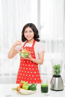 Linda mulher asiática tomando smoothie verde no café da manhã