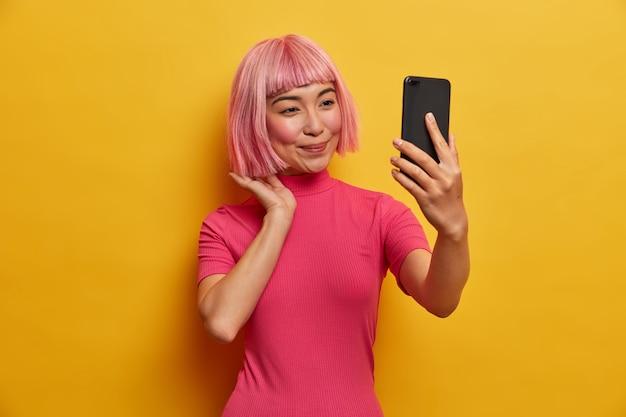 Linda mulher asiática usa gadget para videochamada, arruma o cabelo rosa, olha para a câmera do smartphone, faz selfie