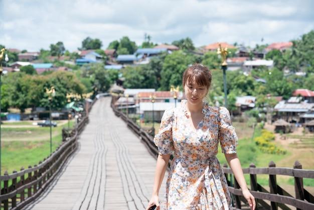 Linda mulher asiática usa postagem casual sozinha na ponte de madeira em sangkhaburi, kanchanaburi, tailândia.