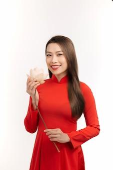 Linda mulher asiática usando ao dai vietnã e segurando uma flor. isolado no branco.