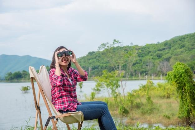Linda mulher asiática usando binóculos para ver os pássaros entre acampar no parque de campismo do lado do lago.