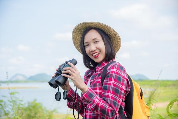 Linda mulher asiática usando binóculos para ver os pássaros entre caminhadas na floresta.