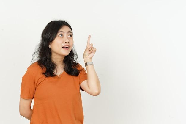 Linda mulher asiática usando camiseta laranja gesto de pensamento isolado no fundo branco