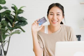 Linda mulher asiática usando computador ou laptop comprando compras on-line