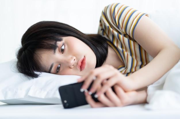 Linda mulher asiática usando o telefone na cama no quarto