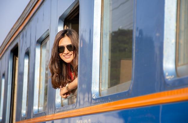 Linda mulher asiática usando óculos de sol, viajar de trem, olhando da janela