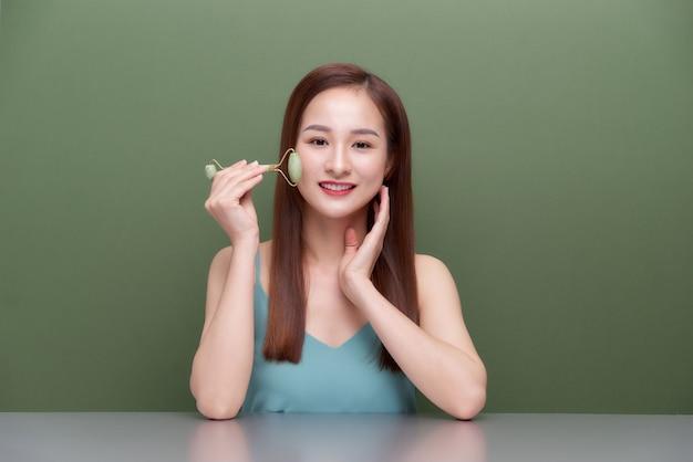 Linda mulher asiática usando rolo de jade para massagear o rosto