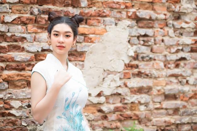Linda mulher asiática usando um cheongsam chinês branco