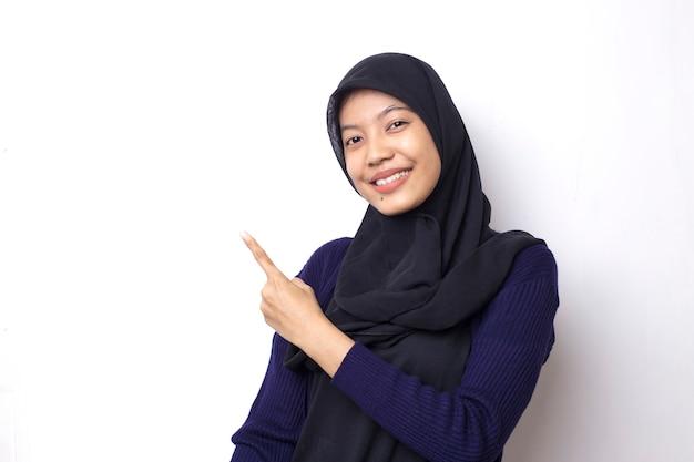 Linda mulher asiática usando um hijab com a ponta da mão no espaço vazio