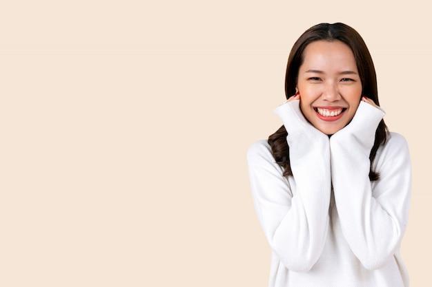 Linda mulher asiática usar roupa casual quente isolada no fundo de cor creme para a temporada de inverno para a moda