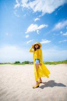 Linda mulher asiática, vestindo roupas amarelas, de pé na praia do mar contra a luz do sol do meio-dia