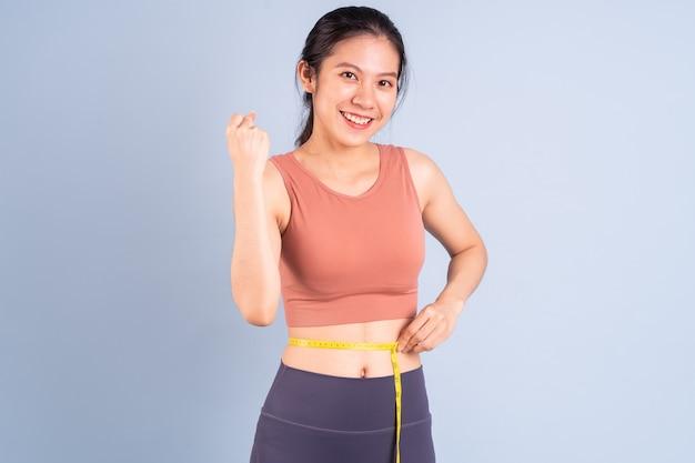 Linda mulher asiática vestindo roupas esportivas e fazendo ioga, fitness e conceito de ginástica