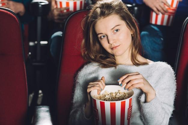 Linda mulher assistindo filme no cinema Foto gratuita