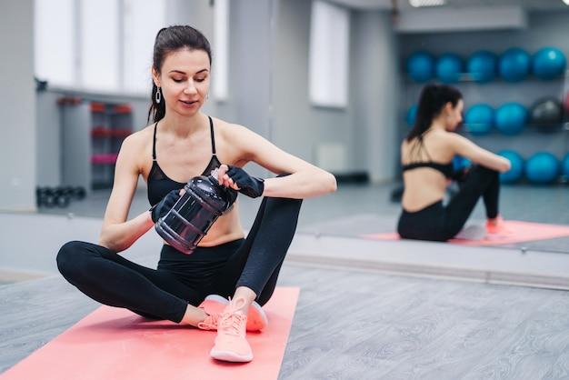 Linda mulher atlética e desportiva sentada no tapete de ioga depois de alguns exercícios com batido de proteína
