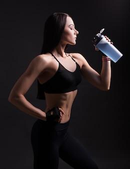 Linda mulher atlética em roupas esportivas bebendo coquetel de proteínas sobre fundo preto