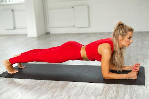Linda mulher atlética em um terno vermelho fazendo ioga na academia