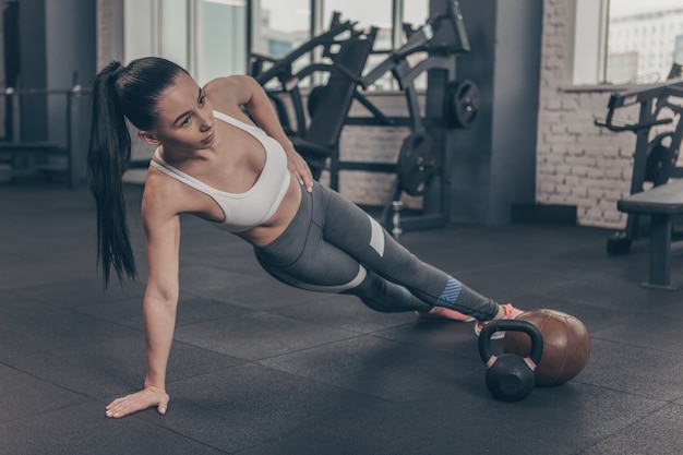 Linda mulher atlética exercitando na academia, fazendo prancha lateral, copie o espaço