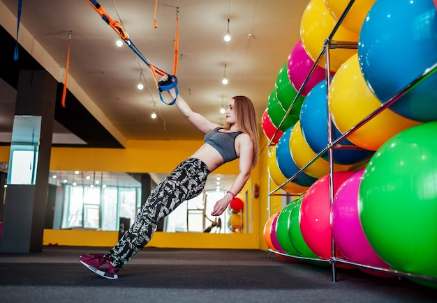 Linda mulher atlética fazendo exercícios usando trx em roupas esportivas na academia