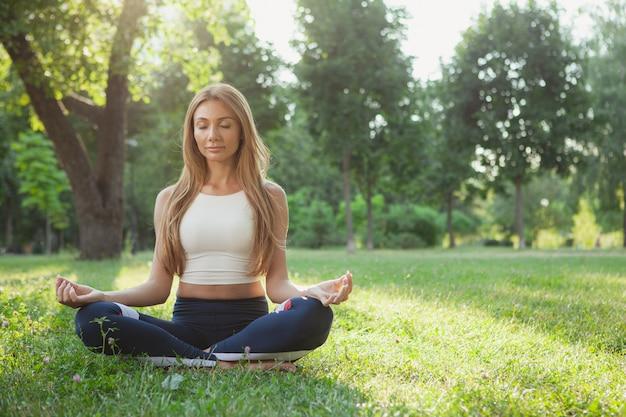 Linda mulher atlética fazendo yoga no parque