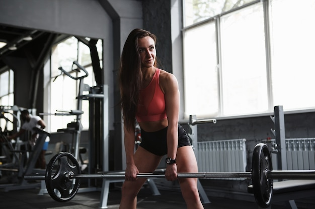 Linda mulher atlética levantando peso no estúdio de esportes