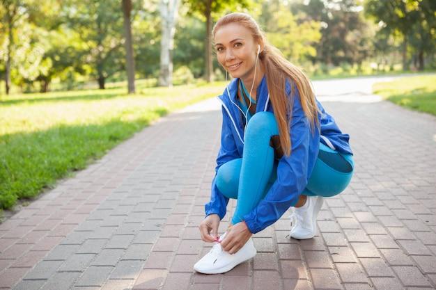 Linda mulher atlética malhando no parque de manhã