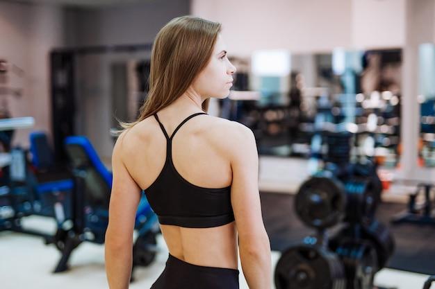 Linda mulher atlética no sportswear posando, atrás e mostrando seu corpo perfeito
