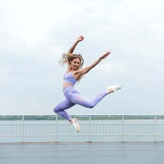 Linda mulher atlética pulando tiro no escuro