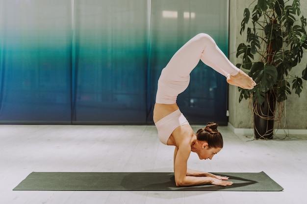 Linda mulher atlética treinando em uma academia, fazendo exercícios de alongamento antes do treino